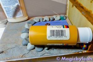 Fairy Door Bookend weighing down clay on wood