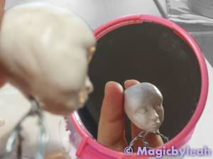 Mentored doll face studying symmetry in the mirror
